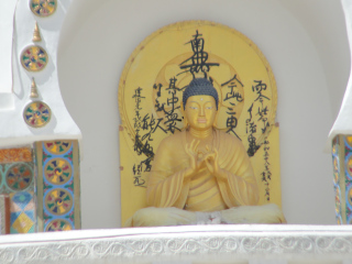 "The golden Buddha at the centre of the stupa depicts the ""Turning Wheel of Dharma""."