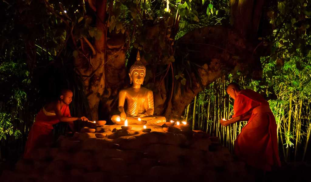 Monks lighting candles at Wat Phan Tao on Makha Bucha Day