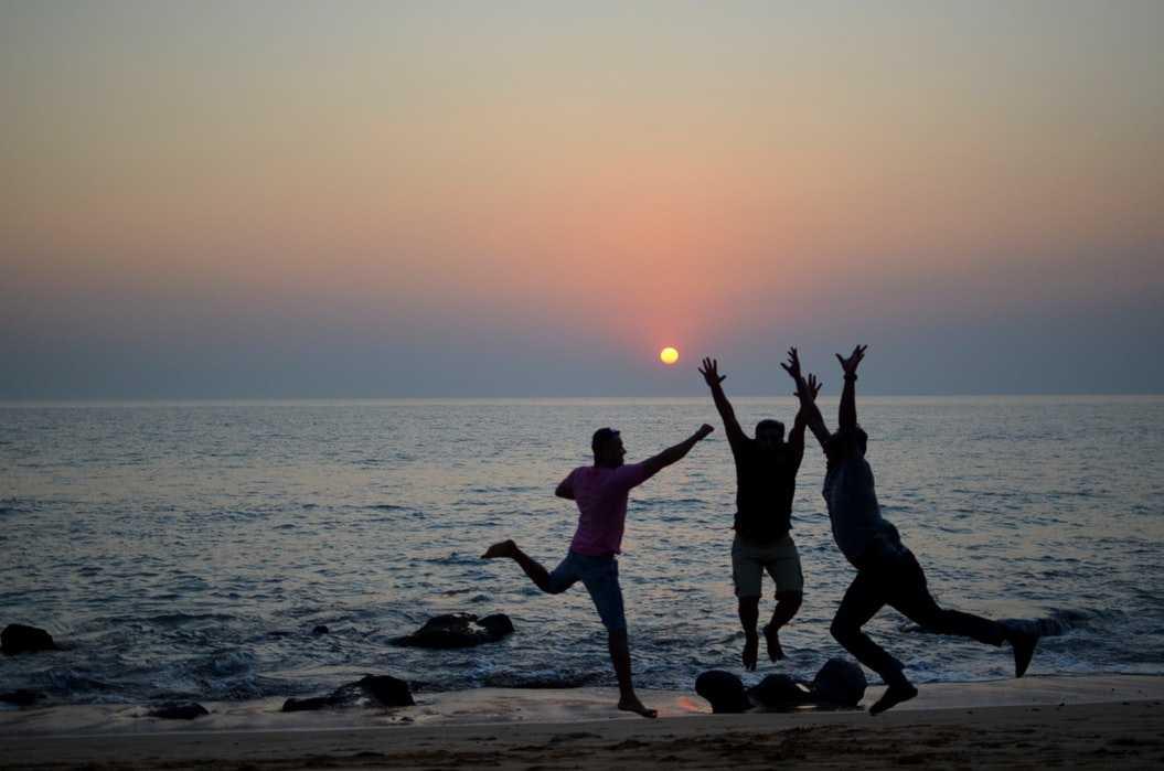 Men enjoying on beach during sunset